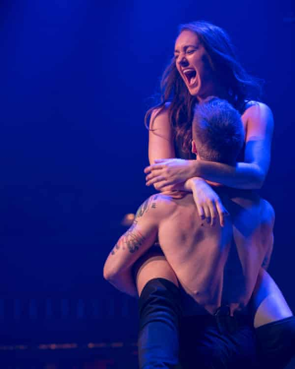 A production shot from an earlier production of Magic Mike Live in which a woman is straddling a performer.