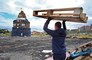 A wooden pallet is carried to a bonfire in the Shankill area of west Belfast