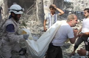 Syrian civil defence workers remove a corpse from the debris after a regime air raid in the al-Kalaseh neighbourhood
