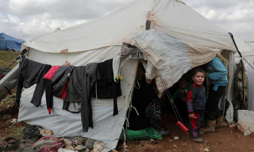 A displaced Syrian child from Idlib, stands outside a tent in Azaz, Syria. The Syrian government's assault has killed around 300 civilians since the start of the year and displaced a million people.