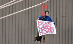 A protester hangs a banner from a coal ship docked in Newcastle harbour on Sunday.