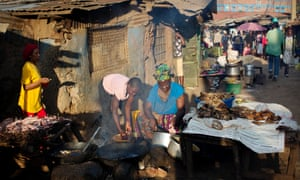 Women cook fish in the evening light to sell to passers by in one of the main streets of Kibera slum in Nairobi.