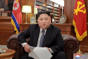 Kim Jong-un makes an address in front of North Korean flags