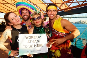 revellers hold a sign saying 'Woke up at 4am to be here'