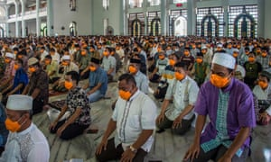 People wearing face masks as a precaution against the COVID-19 coronavirus outbreak attend obligatory Friday prayers at a mosque in Surabaya, East Java, on March 20, 2020.
