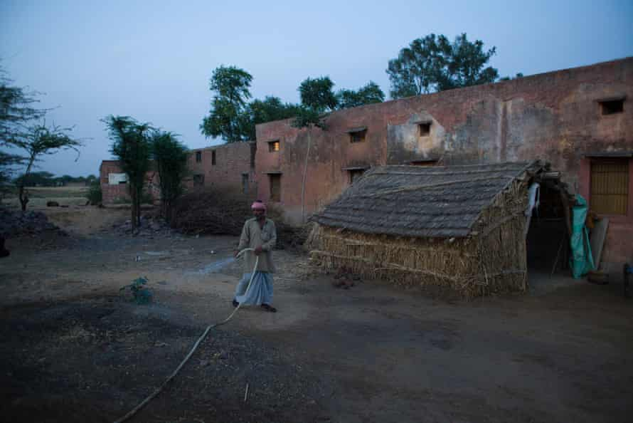 Azim is watering the ground to reduce the dust that gets stirred up in his house in Mewat District, haryana, India, on 31 March 2016.
