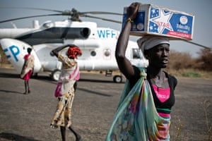 Women carry emergency supplies from a World Food programme helicopter that has just landed in Thanyang, South Sudan