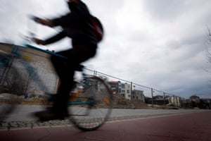 A cyclist passing cobbles marking the former line of the Berlin Wall