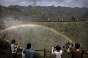A rainbow appears over head as Chinese tourists take pictures of the coal train