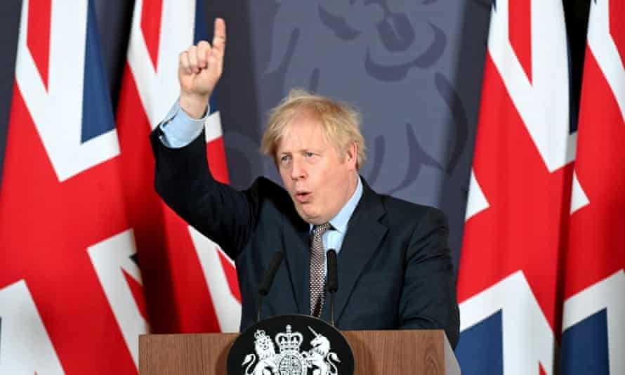 Boris Johnson, flanked by union flags, points to the ceiling at a news conference