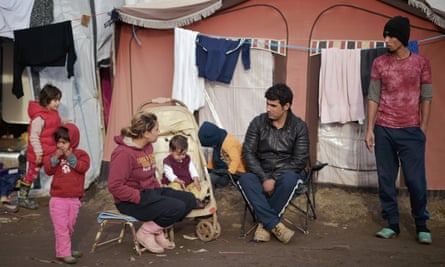 A family sitting outside their tent in the camp known as the 'new iungle' in Calais, France, where thousands are stuck.