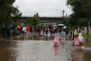 People gather on a street near the Nepean River