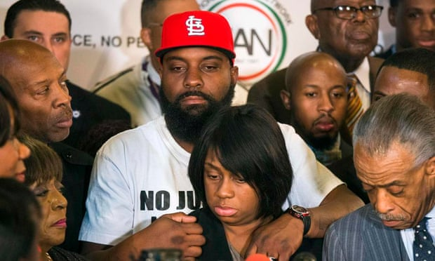 Michael Brown Sr. holds his wife Cal Brown during a news conference with civil rights activist Reverend Al Sharpton in Ferguson, Missouri.