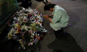 A man prays in Kawasaki where two people were stabbed to death on Tuesday.