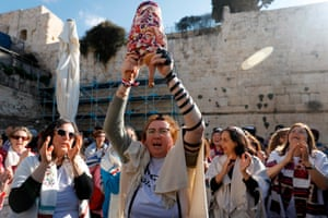 Women of the liberal Jewish movement, wearing traditional prayer shawls for men and holding a Torah scroll, at the egalitarian prayer section of the Western Wall in the Old City of Jerusalem