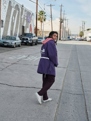 purple jacket with white details, red and white stripe hood shirt, black trousers, white trainers with green stripe around the sole all Balenciaga