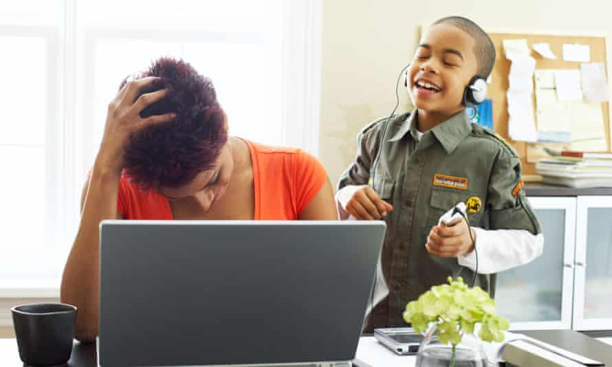 Woman working from home while looking after child