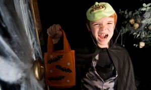 Boy in costume at a Halloween party holding an orange party bag
