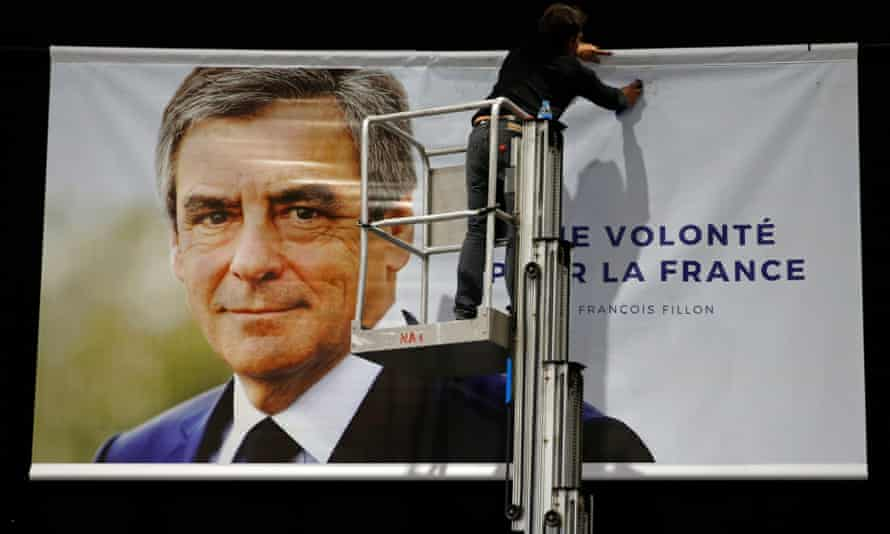A poster for Fillon is put up before a rally in Lille.