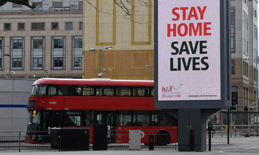 A red London bus drives past a government sign advising people to stay home.