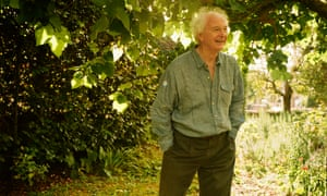 Philip Pullman standing with his hands in his pockets in his garden, smiling