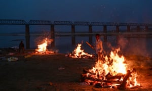 A worker cremates unclaimed bodies of people thought to have died from Covid-19 at a mass crematorium site on the banks of the Ganges rive1 in Allahabad, India. India recorded more than 360,000 coronavirus cases in a day for the 12th day in a row on Monday as the total number of those infected according to Health Ministry data neared 20 million.