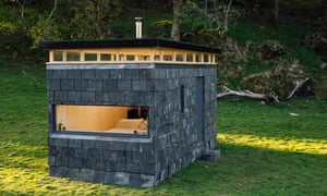 Slate Cabin in a green field on a sunny day.  The stone used for building Slate Cabin enables it to blend into the Welsh landscape, in more rocky areas particularly. One of designer Trias Studio's objectives was to create a relaxing space ideal for a pair of bookworms.