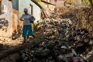 A woman stands in front of the rubbish washed down from the mountain from the rain the night before
