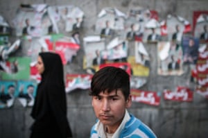 A boy stands in front of electoral posters in downtown Tehran.
