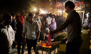 A man roasting corn at a street stall in Darband.