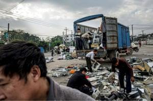 Men sort through old equipment off a truck