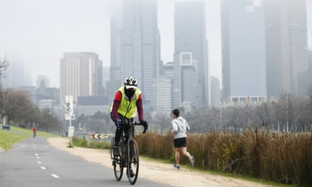 A cyclist is seen wearing a mask along the Yarra River in Melbourne