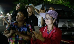 People hold phones outside the Thailand cave rescue