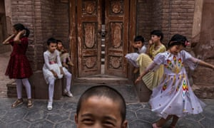 Uighur children sit outside a mosque in Kashgar in June 2017 after it was closed by Chinese authorities.