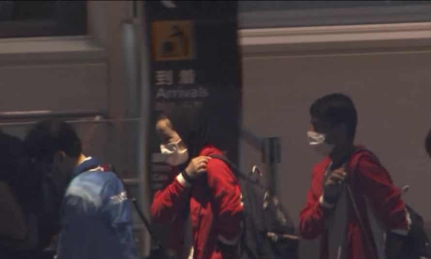 Afghan athletes Zakia Khudadadi, center left, and Hossain Rasouli, center right, arrive at Haneda airport in Tokyo.
