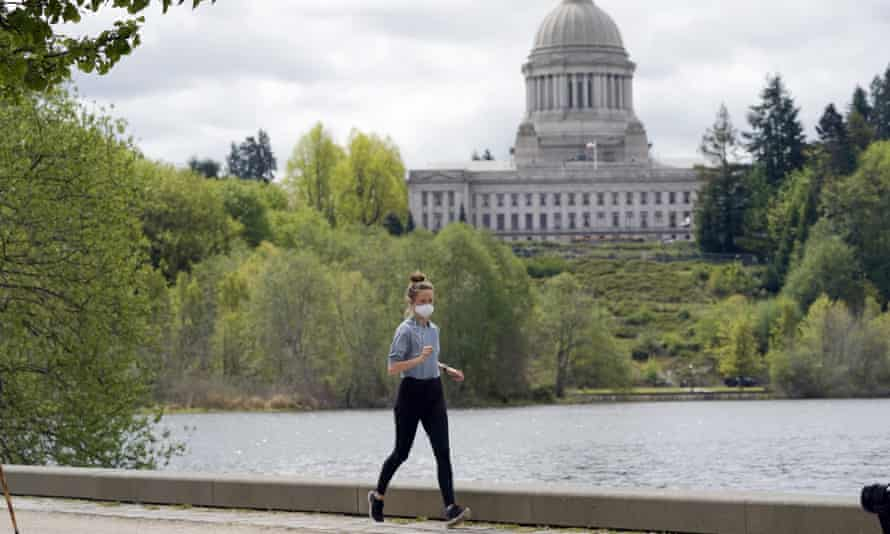 A person wears a mask while jogging near the capitol in Olympia, Washington. The head of the World Health Organization said more than 1bn vaccine doses have been given globally but 82% of them have been administered in high- and upper-middle-income countries.
