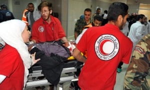 Medics take a wounded man into hospital in Damascus after rockets were fired in Douma on 7 April.