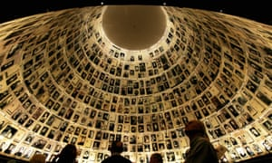 Visitors look at Holocaust pictures at the Hall of Names at the Yad Vashem museum, Jerusalem.
