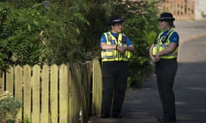 Two PCSOs stand outside a property during a search of a house in Pentwyn.