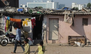 residents of Annawadi go about their daily lives as a luxury hotel rises in the background in Mumbai.