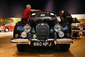 London, England: Auction house assistants polish a 1960 Jaguar XK150S