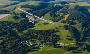 Winging it: a Piper Super Cub flies over Goodwood House.