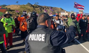 A police officer gestures at demonstrators blocking a road at the base of Hawaii's tallest mountain on Monday.