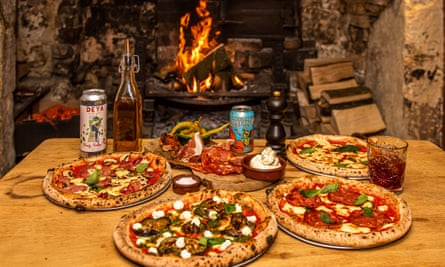 Four pizzas amid cans of local beer in front of a fire at The Stump, Cirencester, Gloucestershire, UK