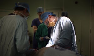 people in scrubs performing an operation at Queen's Elizabeth Hospital, Birmingham