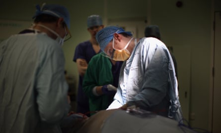 A surgeon performs a neck and throat operation
