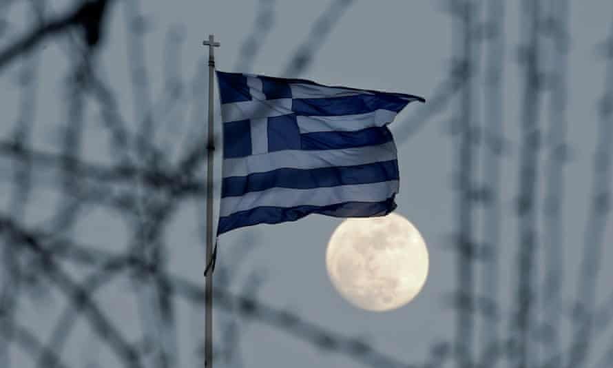 A Greek national flag flutters as the moon rises in Athens.