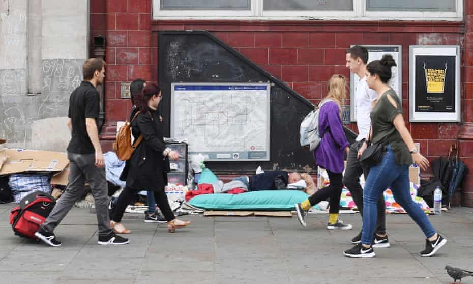 Pedestrians walk past a homeless man sleeping next to Camden Town underground station in London, 30 July 2018