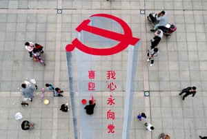 A man working on a 3D street painting of the emblem of the Chinese Communist party to celebrate the upcoming congress in Xiayi in central Henan province