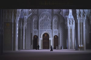 Casablanca, Morocco. Three people walk amid the grand architecture of a temple that dwarfs them.  The architecture of Casablanca towers above the day-to-day life of its inhabitants like a giant and intricate universe.